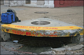 storm drain with Trash Kills Crabs painted on it - by Erica Goldman