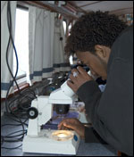 student looking at a microscope