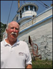 Chuck Epifanio next to the decaying fishing boat was once the Flagship Restaurant. Credit: Michael W. Fincham