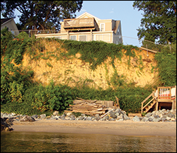 Erosion along the length of the cliffs threatens a home. Credit: David Brownlee