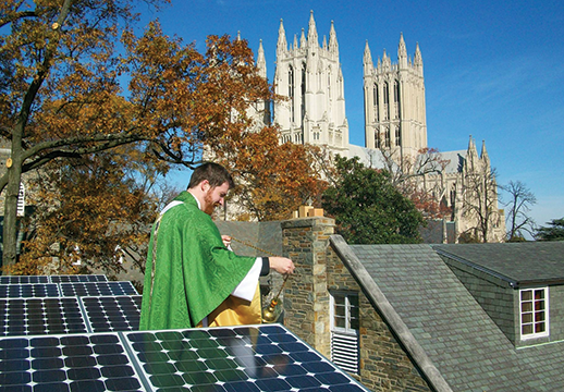 Jered Weber-Johnson blesses rooftop solar panels at St. Alban's Episcopal Church. Photograph, Carlo La Porta