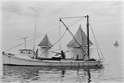 Two kinds of oystering: a patent tonger with his hydraulic rig. Photograph courtesy of the Chesapeake Bay Maritime Museum