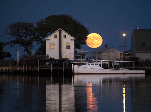 A blood moon rises over a waterman's home and workboat on Smith Island. Photograph courtesy of David Harp