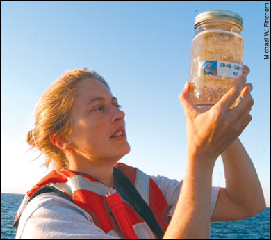 Elizabeth North holding a jar of crab larvae