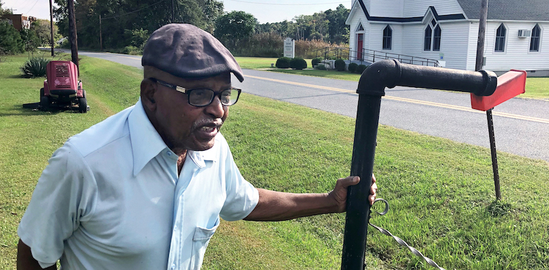Despite heat and mosquitoes, Luther Cornish mows his lawn several times a week in the summer to keep the drainage area clear.